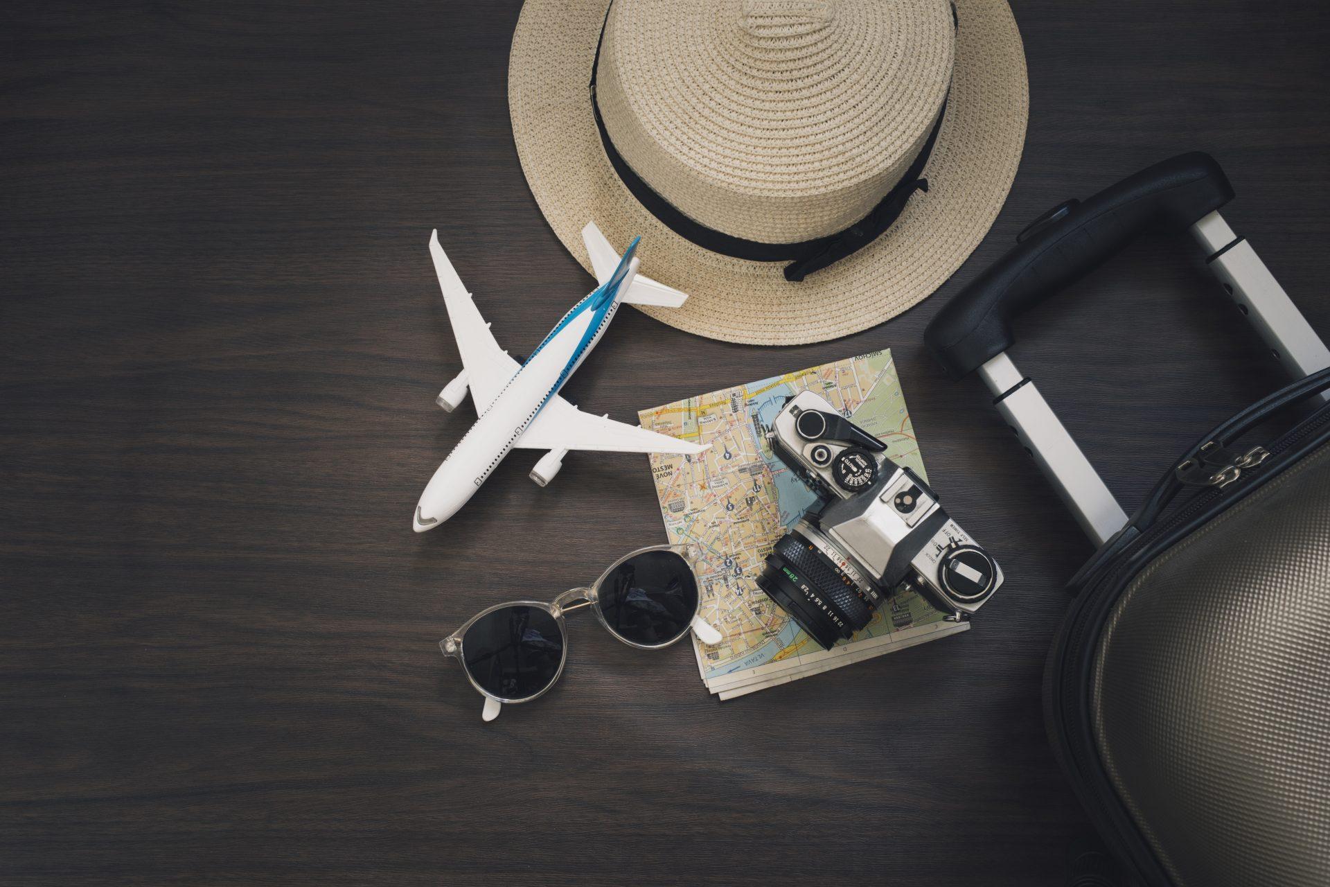 Regali per viaggiatori: macchina fotografica, trolley, mappamondo, biglietto aereo